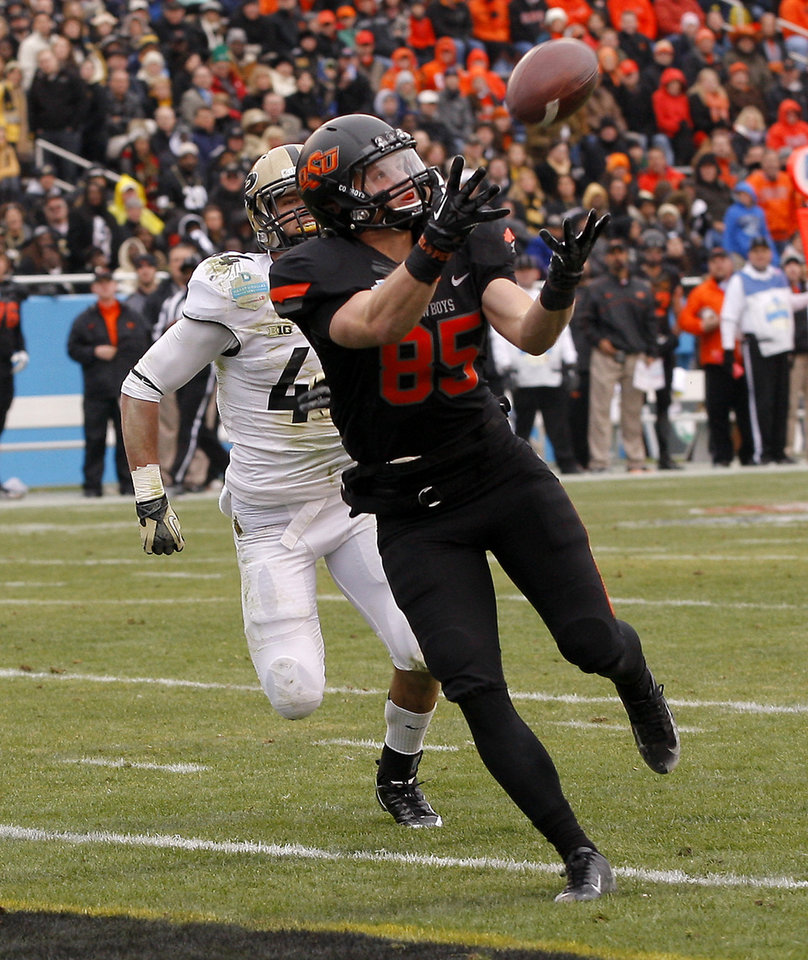 Photo - Oklahoma State's Blake Webb (85) catches a touchdown pass in front Purdue's Landon Feichter (44) during the Heart of Dallas Bowl football game between Oklahoma State University and Purdue University at the Cotton Bowl in Dallas, Tuesday, Jan. 1, 2013. Oklahoma State won 58-14. Photo by Bryan Terry, The Oklahoman