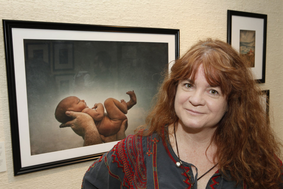 Photo - Oklahoma City photographer M.J. Alexander is shown with her portrait of Brandy McDonnell's 21-month-old daughter Brenna, which was taken when the girl was just 100 hours old and is part of Alexander's