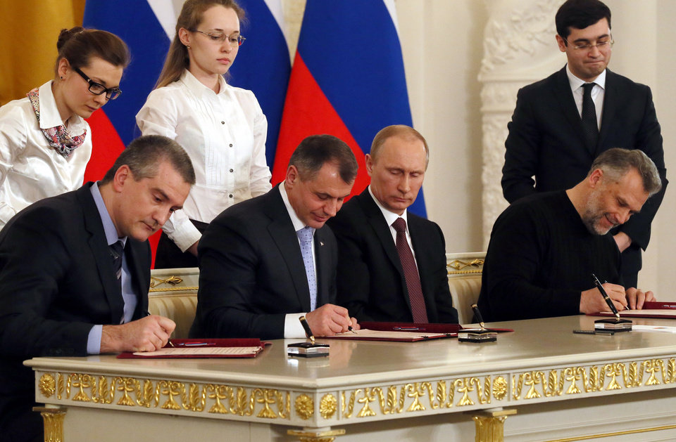 Photo - Russian President Vladimir Putin, second right, looks on as Crimean leaders, Speaker of Crimean legislature Vladimir Konstantinov, second left, Crimean Premier Sergei Aksyonov, left, and Sevastopol mayor Alexei Chalyi, right, sign a treaty for Crimea to join Russia in the Kremlin in Moscow,  Tuesday, March 18, 2014. President Vladimir Putin on Tuesday signed a treaty to incorporate Crimea into Russia, describing the move as the restoration of historic injustice and a necessary response to what he called the Western encroachment on Russia's vital interests.  (AP Photo/Sergei Ilnitsky, Pool)