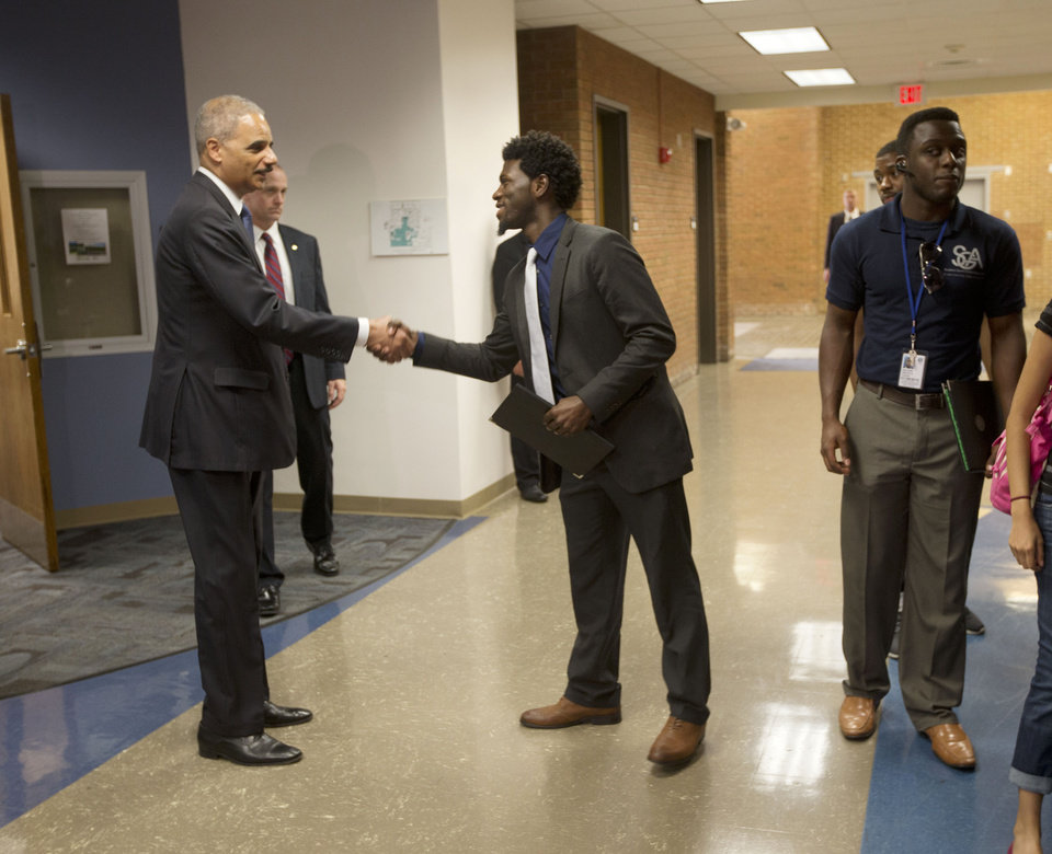Photo - Attorney General Eric Holder shakes hands with Bradley J. Rayford, 22 following his meeting at St. Louis Community College Florissant Valley in Ferguson, Mo., Wednesday, Aug. 20, 2014. Holder arrived in Missouri on Wednesday, a small group of protesters gathered outside the building where a grand jury could begin hearing evidence to determine whether a Ferguson police officer who shot 18-year-old Michael Brown should be charged in his death.  (AP Photo/Pablo Martinez Monsivais, Pool)