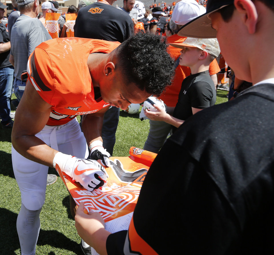 Photo - Chuba Hubbard (30) signs a poster for a fan after the spring football game for the Oklahoma State Cowboys (OSU) at Boone Pickens Stadium in Stillwater, Okla., Saturday, April 28, 2018. Photo by Nate Billings, The Oklahoman