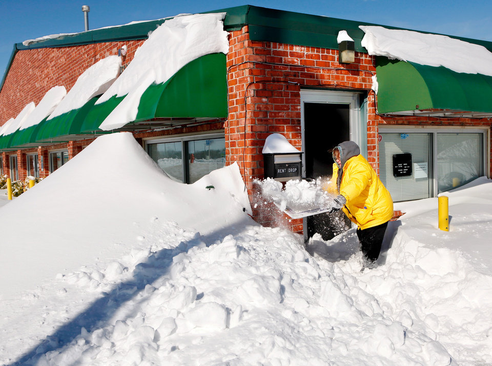 Photo - Stella Bell-Craig found a plastic wall calendar was more useful than a shovel Wednesday morning as she dug through deep snow to get to the office door at her business, GateKeeper Self Storage at 3221 E. Memorial Road in Edmond. Central Oklahoma residents began digging out from beneath nearly a foot of snow covering the ground Wednesday, Feb, 2, 2011, after yesterday's winter snowstorm. Photo by Jim Beckel, The Oklahoman
