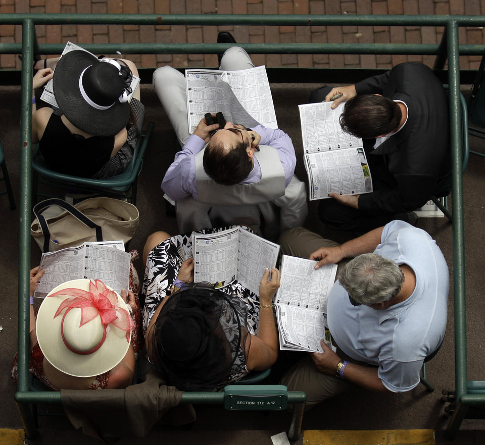 Photo - Spectators study their race programs before the 138th Kentucky Derby horse race at Churchill Downs Saturday, May 5, 2012, in Louisville, Ky. (AP Photo/Charlie Riedel)  ORG XMIT: DBY143