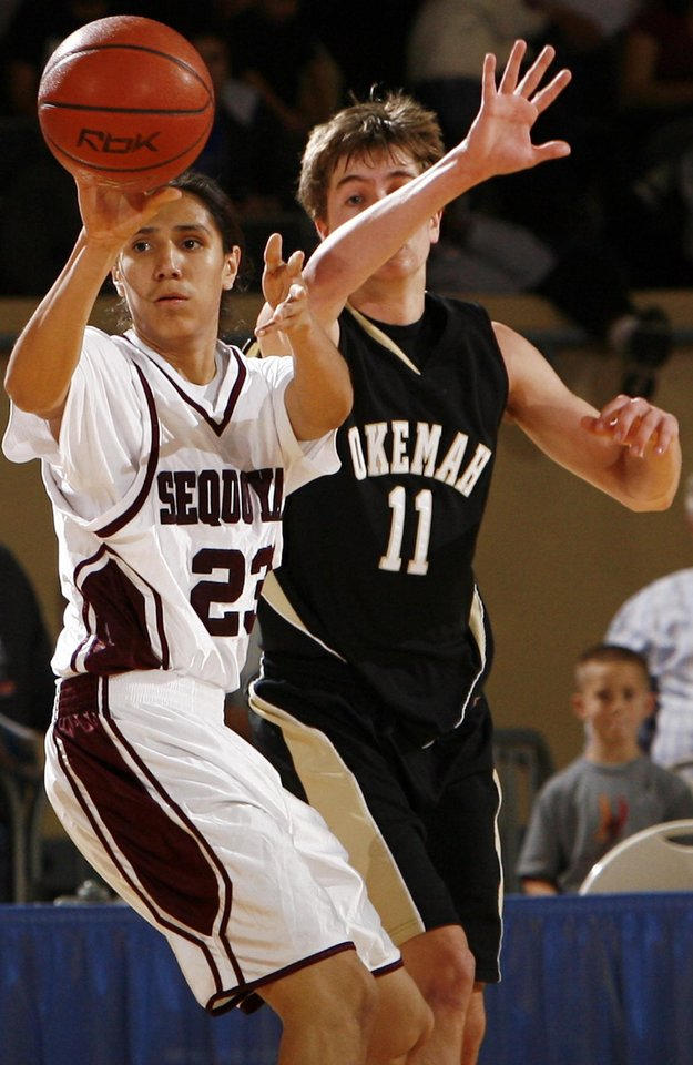 Photo - Sequoyah-Tahlequah's Cody Fourkiller (23) passes away from Okemah's John Palmer (11) during the 3A boys semifinal game between Okemah and Sequoyah-Tahlequah in the Oklahoma High School Basketball Championships at State Fair Arena in Oklahoma City, Friday, March 13, 2009. Okemah won to advance to the finals. PHOTO BY NATE BILLINGS, THE OKLAHOMAN