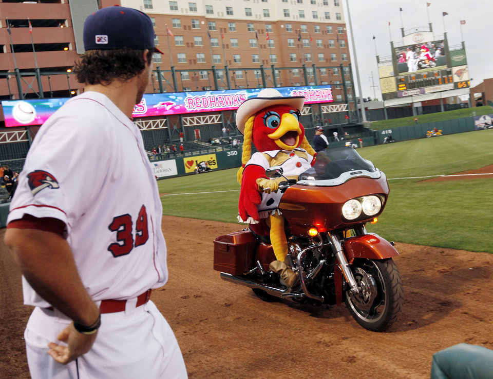 Oklahoma City's Brett Wallace (39) watches mascot Ruby ride a motorcycle before the 2012 opening day baseball game between the Oklahoma City RedHawks and the Memphis Redbirds at the Chickasaw Bricktown Ballpark in Oklahoma City, Thursday, April 5, 2012. Photo by Nate Billings, The Oklahoman