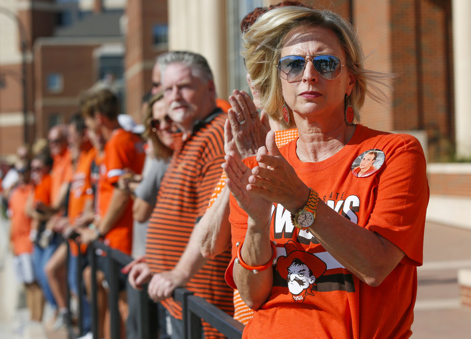 Photo -  Phyllis Cornelius, mother of OSU quarterback Taylor Cornelius, claps during The Walk on Hester Street in Stillwater before Thursday's game against Missouri State. [Photos by Nate Billings, The Oklahoman]