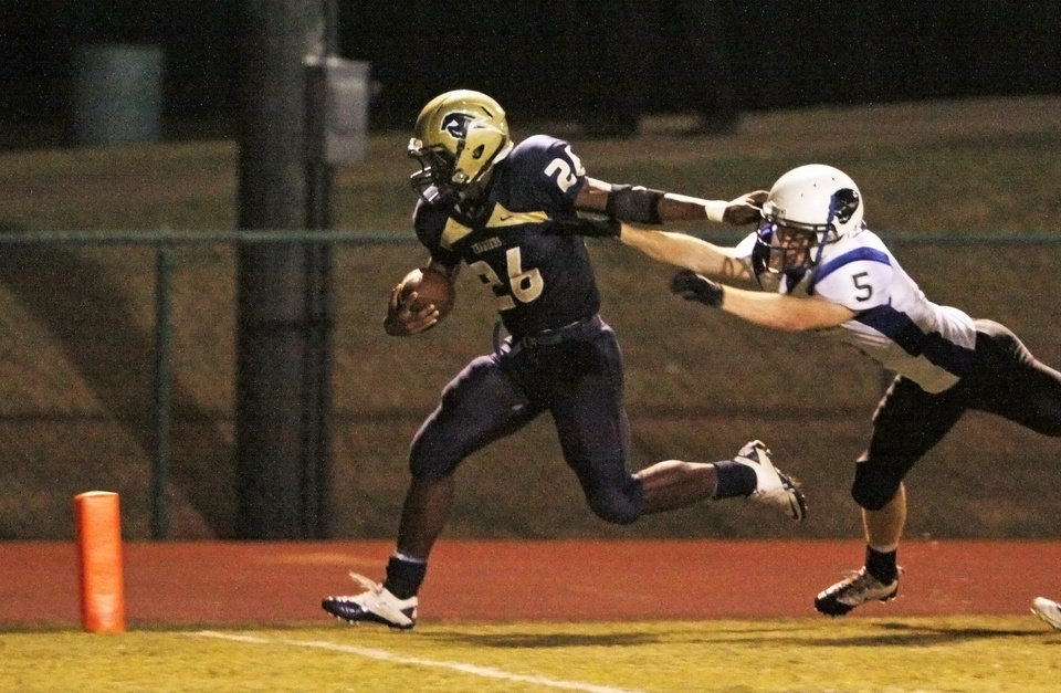 Photo - Barry Sanders, Jr. pushes away Justus McGuire to get to the end zone for a 4th time in the first half during the high school football game between Heritage Hall and NOAH in Oklahoma City, Friday, Oct. 1, 2010. Photo by Doug Hoke, The Oklahoman.