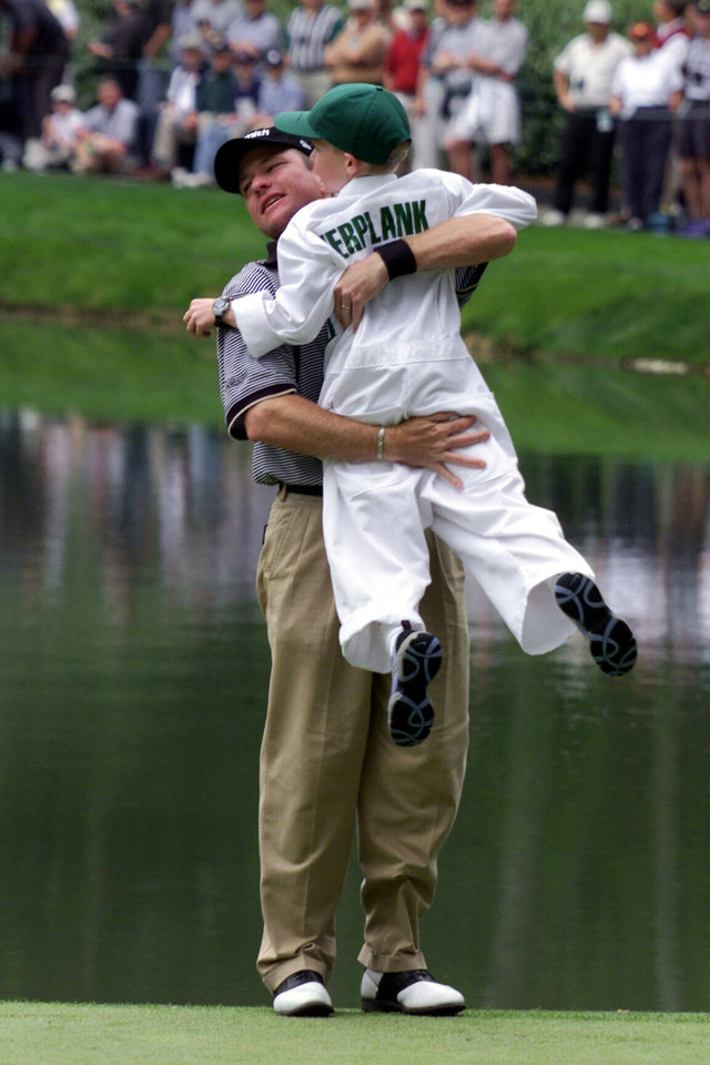 Photo - GOLFER, Scott Verplank celebrates his hole-in-one on the 9th green with his son, Scottie, during the Par 3 Contest at the Augusta National Golf Club in Augusta, Ga., Wednesday, April 4, 2001, as part of the Masters festivities.  First round Masters play begins Thursday.   (AP Photo/Doug Mills)