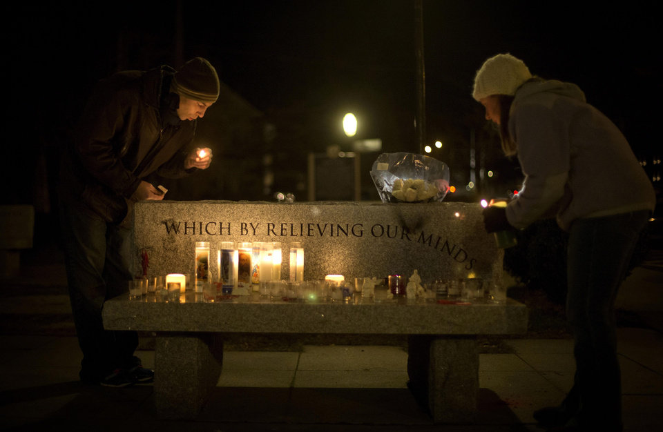 Photo - Brian Tenenhaus, left, blows out a match after lighting a candle at a vigil outside the Edmond Town Hall with Lauren Foster, right, Saturday, Dec. 15, 2012, in Newtown, Conn. A gunman walked into Sandy Hook Elementary School in Newtown Friday and opened fire, killing 26 people, including 20 children. (AP Photo/David Goldman) ORG XMIT: CTDG151