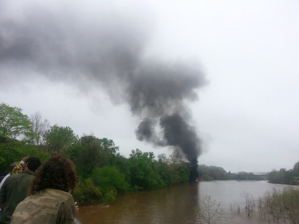 Photo - In this mobile phone photo provided Allison Hallock, people watch smoke rise from a bridge over the James river after several CSX tanker cars carrying crude oil derailed, Wednesday, April 30, 2014, in Lynchburg, Va. Authorities evacuated numerous buildings Wednesday after the derailment. (AP Photo/Ali Hallock) MANDATORY CREDIT