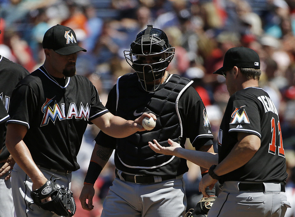 Photo - Miami Marlins pitcher Mike Dunn, left, is relieved by manager Mike Redmond, right, in the eighth inning of a baseball game against the Atlanta Braves, Wednesday, April 23, 2014, in Atlanta. (AP Photo/David Goldman)