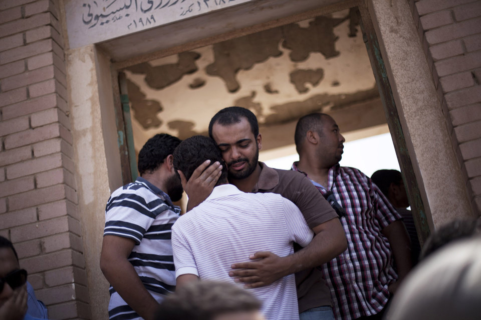 Photo - A friend of Ammar Badie, 38, killed by Egyptian security forces Friday during clashes in Ramses Square, and also son of Muslim Brotherhood's spiritual leader Mohammed Badie, comforts a relative while attending his burial in Cairo's Katameya district, Egypt, Sunday, Aug. 18, 2013. Egypt increased security at the Supreme Constitutional Court building ahead of planned mass rallies by supporters of the country's ousted President Mohammed Morsi. (AP Photo/Manu Brabo)