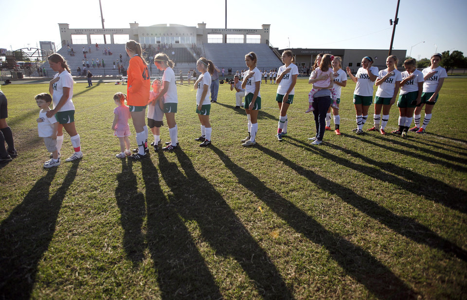 Photo - Bishop McGuinness girls soccer team members and several students from the Good Shepherd Catholic School at Mercy sing the National Anthem before a soccer game Tuesday at Bishop McGuinness,  801 NW 50.  SARAH PHIPPS - SARAH PHIPPS