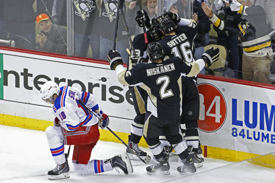 Photo - Pittsburgh Penguins' Jussi Jokinen, center not shown, celebrates his goal with teammates as New York Rangers' Marc Staal (18) kneels on the ice in the third period of game 2 of a second-round NHL playoff hockey series against the New York Rangers in Pittsburgh Sunday, May 4, 2014. The Penguins won 3-0, to tie the series at 1-1. (AP Photo/Gene J. Puskar)