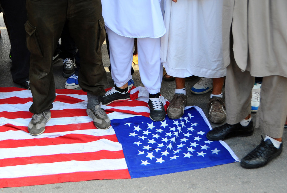 In this photo taken Wednesday, Sept. 12, 2012, Islamic Tunisian protesters step on a U.S. flag during a protest outside the outside the U.S. embassy in Tunis, as part of widespread anger across the Muslim world about a film ridiculing Islam's Prophet Muhammad. Leaked conversations in which alcohol bans and the imposition of religious law were mentioned have raised fears Tunisia�s new government may not be moderate at all, especially in the context of mob attacks on the U.S. Embassy that coincided with the American ambassador�s killing in neighboring Libya. (AP Photo/Hassene Dridi)