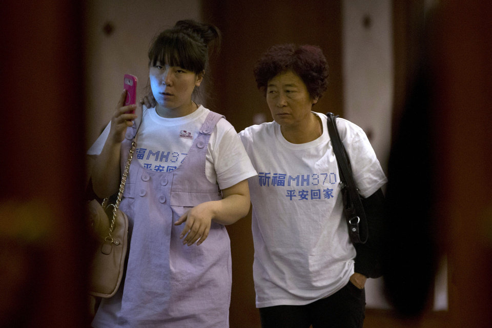 Photo - Relatives of Chinese passengers aboard the missing Malaysia Airlines, MH370, walk out from a meeting room in a hotel wearing a t-shirt which reads