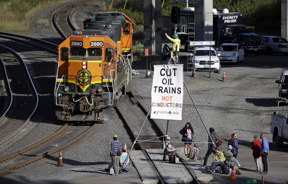 Photo - Abby Brockway waves from atop a tripod erected on train tracks to a pair of engines passing on an adjacent track Tuesday, Sept. 2, 2014, in Everett, Wash. About a dozen demonstrators blocked the tracks at a Burlington Northern Santa Fe yard to protest oil and coal export terminals in the Northwest. (AP Photo/Elaine Thompson)