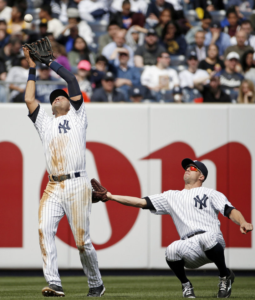 Photo - New York Yankees left fielder Brett Gardner, right, backing up New York Yankees shortstop Derek Jeter on Matt Wieters' fifth-inning pop out in a baseball game against the Baltimore Orioles at Yankee Stadium in New York, Tuesday, April 8, 2014.  (AP Photo/Kathy Willens)