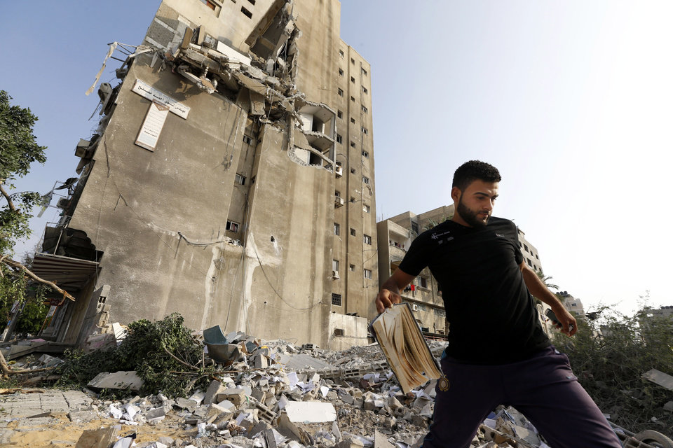 Photo - Palestinians inspect the damage to Al-Shalam (Peace) tower, destroyed by an overnight Israeli strike, Tuesday, July 22, 2014. A high-level attempt by the U.N. chief and the U.S. secretary of state to end deadly Israel-Hamas fighting was off to a rough start Monday: Gaza's Hamas rulers signaled they won't agree to an unconditional cease-fire, Israel's prime minister said he'll do whatever is necessary to keep Israelis safe from Hamas attacks. Gaza health officials say hundreds Palestinians have died since the beginning of Israel's campaign in the Gaza Strip since the ground operation began Thursday. (AP Photo/Lefteris Pitarakis)