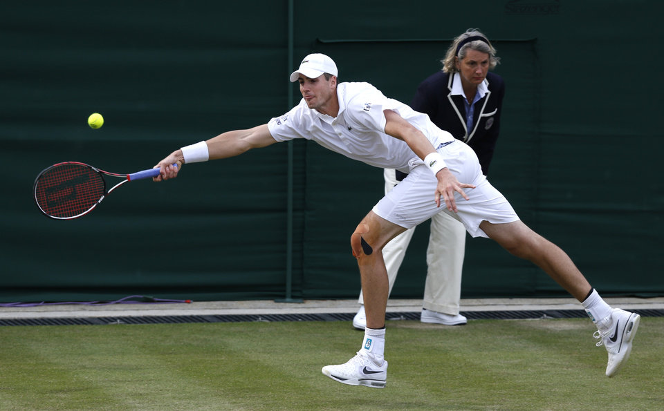 Photo - John Isner of the U.S. plays a return to Jarkko Nieminen of Finland during their men's singles match at the All England Lawn Tennis Championships in Wimbledon, London, Thursday, June 26, 2014. (AP Photo/Sang Tan)
