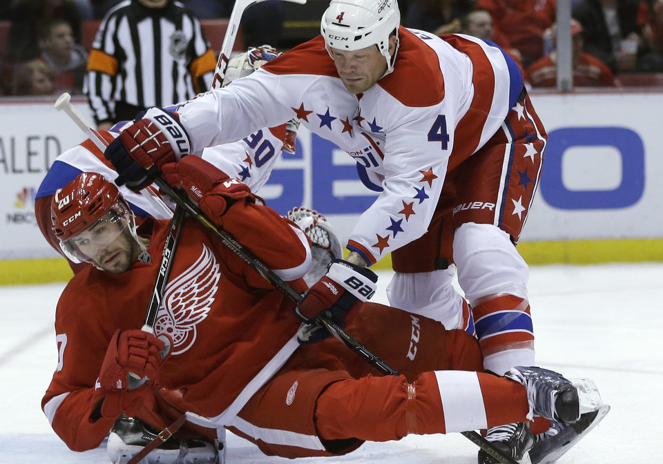 Photo - Detroit Red Wings left wing Drew Miller (20) is checked by Washington Capitals defenseman John Erskine (4) during the second period of an NHL hockey game in Detroit, Friday, Jan. 31, 2014. (AP Photo/Carlos Osorio)
