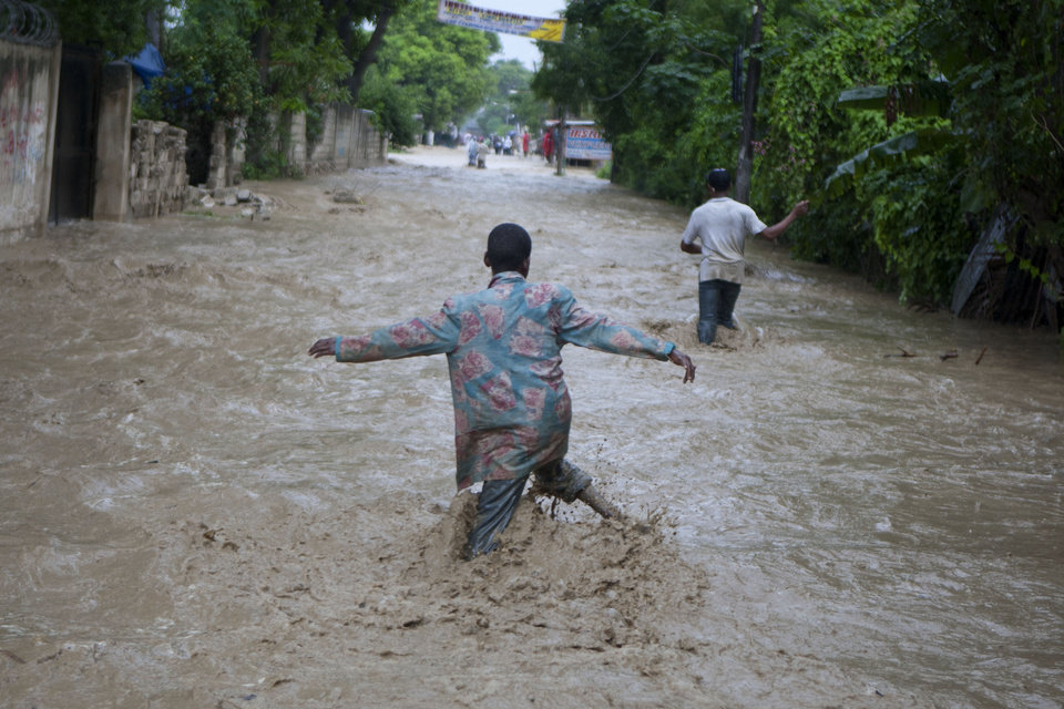 Photo -   Residents wade through a flooded street caused by heavy rains from Hurricane Sandy in Port-au-Prince, Haiti, Thursday, Oct. 25, 2012. Hurricane Sandy rumbled across mountainous eastern Cuba and headed toward the Bahamas on Thursday as a Category 2 storm, bringing heavy rains and blistering winds. (AP Photo/Dieu Nalio Chery)
