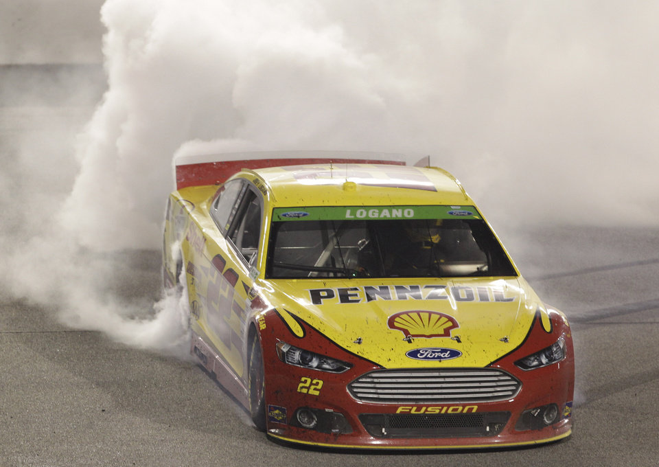 Photo - Joey Logano (22) does a burnout after winning the NASCAR Sprint Cup auto race at Richmond International Raceway in Richmond, Va., Saturday, April 26, 2014. (AP Photo/Steve Helber)