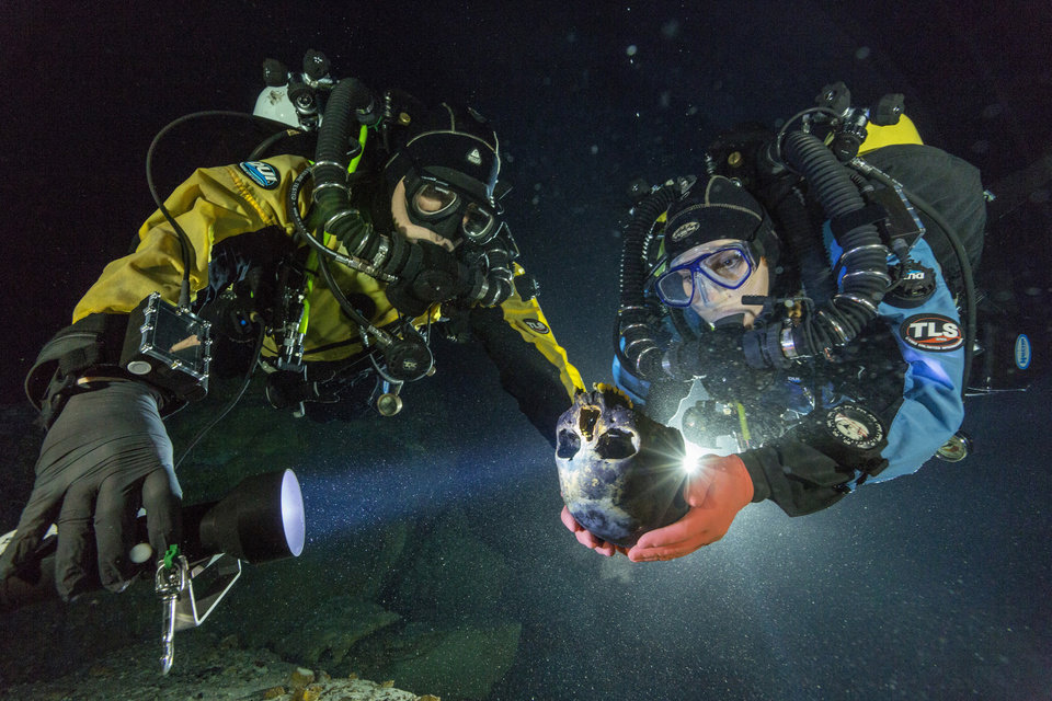 Photo - In this June 2013 photo provided by National Geographic, divers Alberto Nava and Susan Bird transport the Hoyo Negro skull to an underwater turntable so that it can be photographed to create a 3-D model in an underwater cave in Mexico's Yucatan Peninsula. Thousands of years ago, a teenage girl fell into this deep hole and died. Now, her skeleton and her DNA are helping scientists study the origins of the first Americans. An analysis of her remains was released Thursday, May 15, 2014 by the journal Science. Her DNA links her to an ancient land bridge connecting Asia and North America, and suggests she shares ancestors with the modern native peoples of the Americas. (AP Photo/National Geographic, Paul Nicklen)