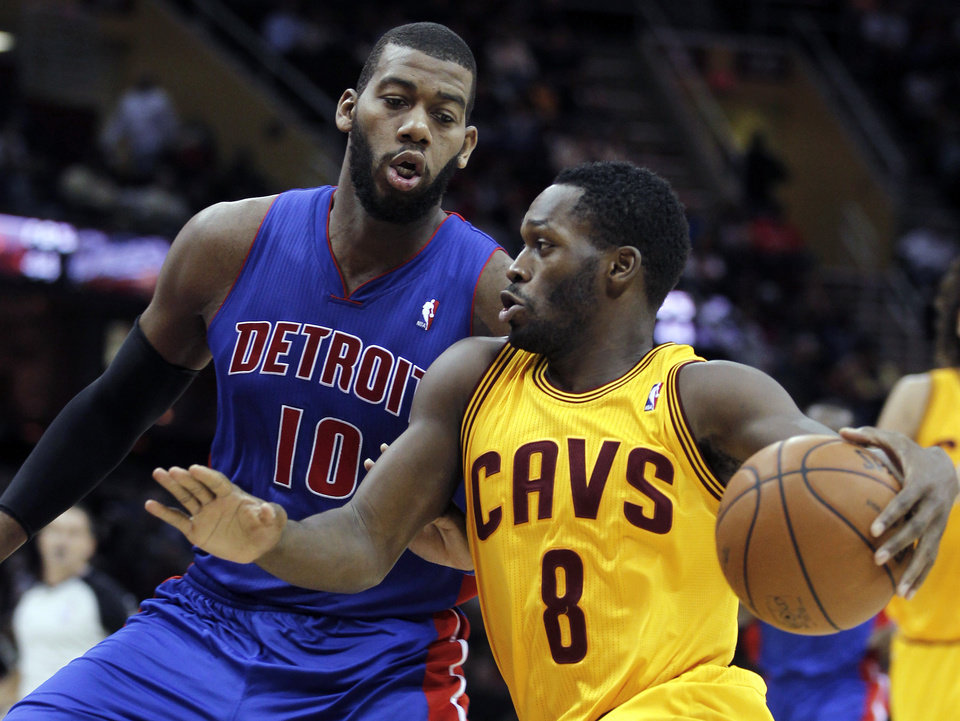 Photo - Cleveland Cavaliers' Jeremy Pargo (8) drives past Detroit Pistons' Greg Monroe (10) during the second quarter of an NBA basketball game Saturday, Dec. 8, 2012, in Cleveland. (AP Photo/Tony Dejak)