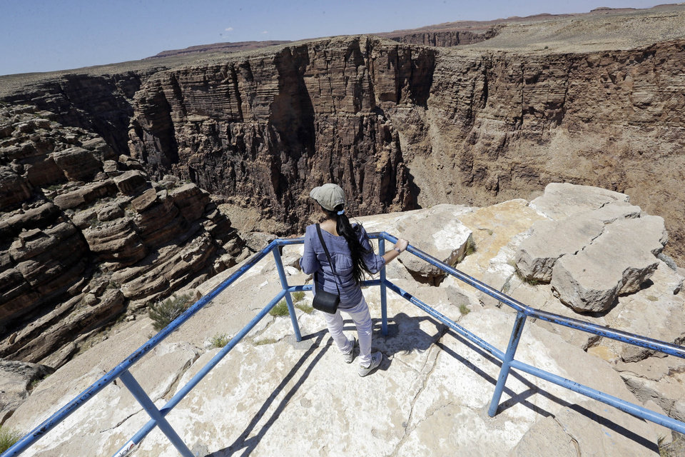 Photo - A unidentified tourist looks from a view point along the Little Colorado River Gorge Saturday, June 22, 2013, on the Navajo reservation near Cameron, Ariz., outside the boundaries of Grand Canyon National Park, near where Nik Wallenda, the Florida-based daredevil, will bid to walk on a tightrope stretched across the Little Colorado River Gorge.  The event, which will be broadcast on live television at 8 p.m. EDT on Sunday with a 10 second delay. Wallenda will walk a third of a mile across a wire suspended 1,500 feet above the river. (In comparison, the Empire State Building in New York City is 1,454 feet high). (AP Photo/Rick Bowmer)