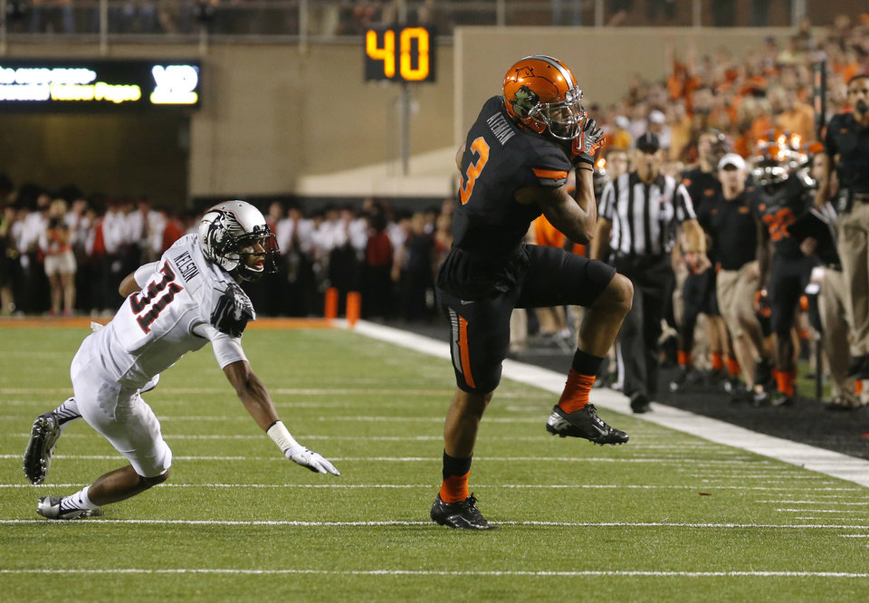 Photo - Oklahoma State's Marcell Ateman (3) catches a pass in front of Texas Tech's Justis Nelson (31) during a college football game between the Oklahoma State Cowboys (OSU) and the Texas Tech Red Raiders at Boone Pickens Stadium in Stillwater, Okla., Thursday, Sept. 25, 2014. Photo by Bryan Terry, The Oklahoman