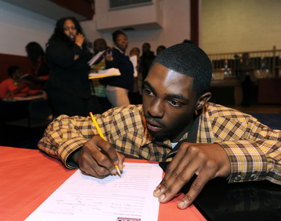 Photo - In this April 23, 2014 photo, Davon Tremble, of Detroit, fills out an application at a job fair at the Matrix Center in Detroit. The Labor Department reports the number of people who applied for unemployment benefits last week on Thursday, May 15, 2014. (AP Photo/The Detroit News, David Coates)
