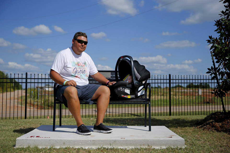 Photo - Cashion assistant coach Cale Cochran and his son Jaxon listen to music while sitting on a bench dedicated to his late wife Jacie Cochran before a high school football game between Cashion and Perry in Cashion, Okla., Friday, Sept. 4, 2020. Cochran's wife, Jacie, died July 2 shortly after giving birth to their son Jaxon. [Bryan Terry/The Oklahoman]
