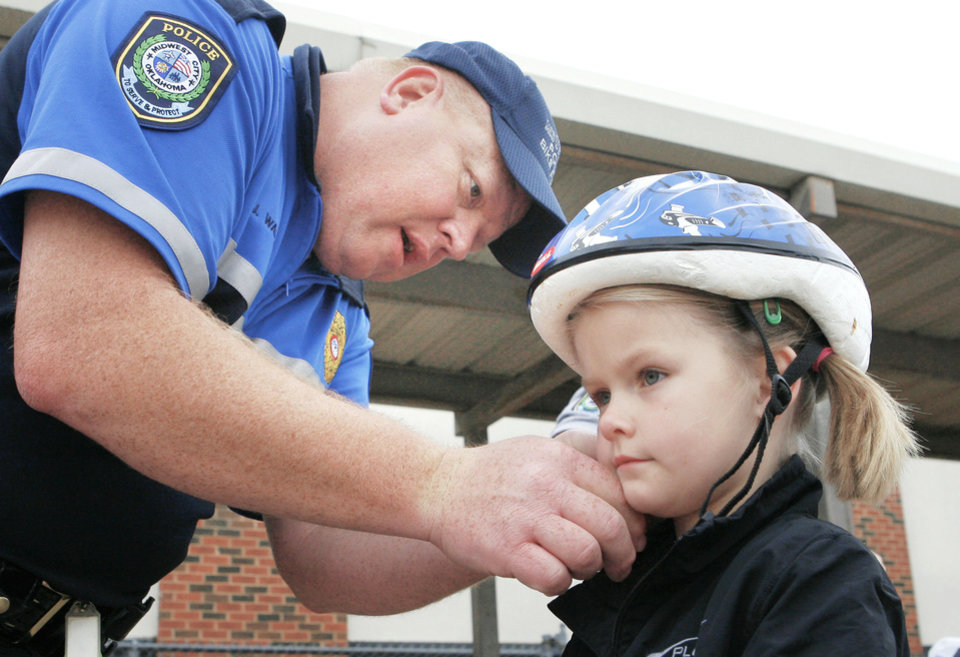 boldMidwest City police Sgt. Joel Warner checks the fit of Berklie Foster's helmet at a bike rodeo and safety fair at Soldier Creek Elementary School.  OKLAHOMAN ARCHIVE PHOTO BY PAUL HELLSTERN