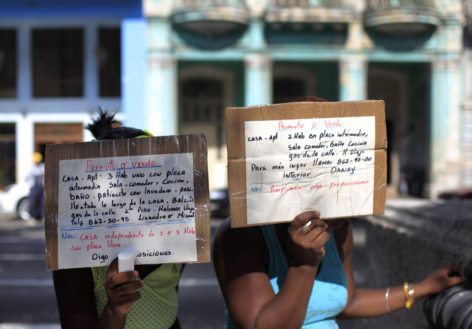 Photo - In this April 20, 2013 photo, women hold up homemade signs advertising homes for sale or rent, in Havana, Cuba. A baffling, sometimes bizarre real estate market has emerged in the year and a half since President Raul Castro legalized private home sales in Cuba, for the first time in five decades. While trade in homes is now legal, the people who bring buyers together with sellers are not. (AP Photo/Franklin Reyes)