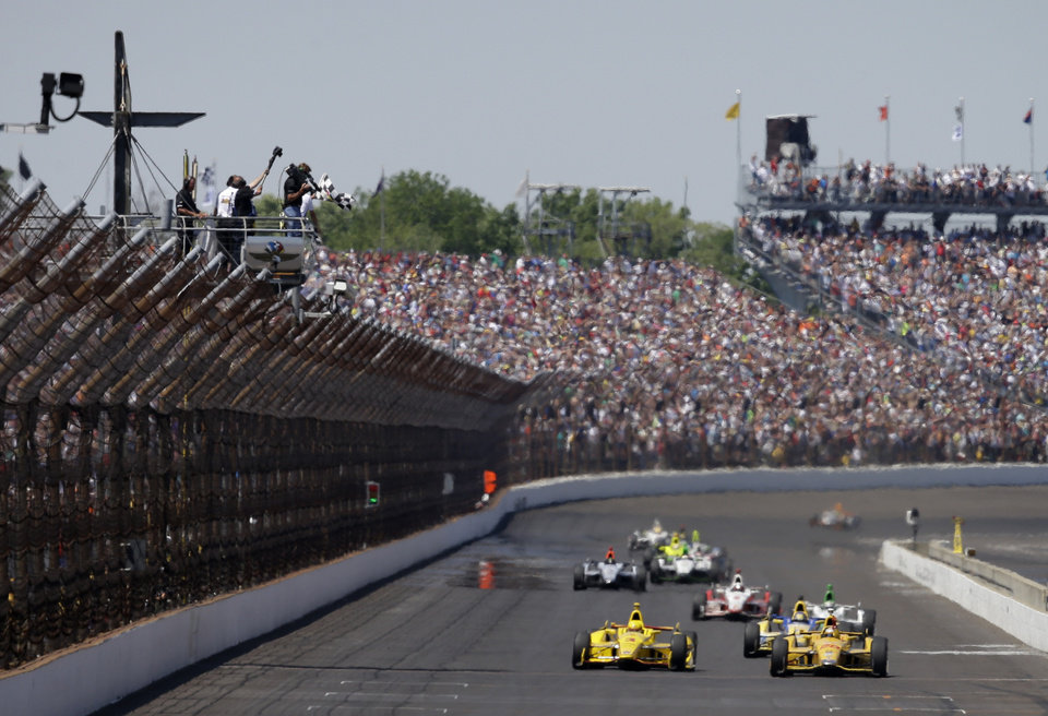 Photo - Ryan Hunter-Reay celebrates as he takes the checkered flag to win  the 98th running of the Indianapolis 500 IndyCar auto race at the Indianapolis Motor Speedway in Indianapolis, Sunday, May 25, 2014. (AP Photo/Darron Cummings)