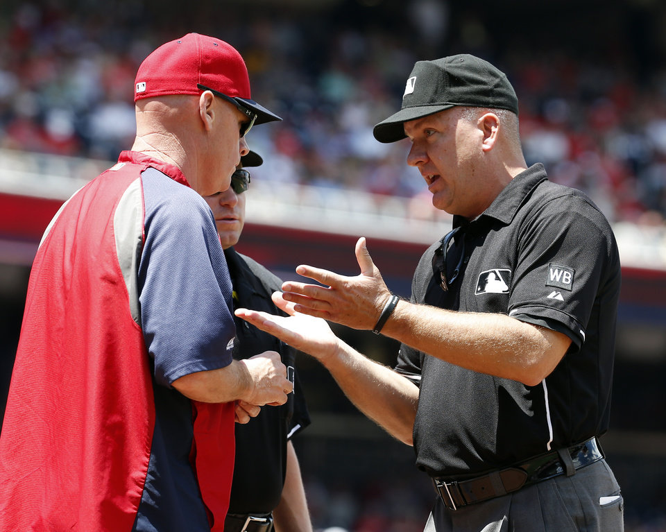 Photo - Washington Nationals manager Matt Williams, left, asks for a review from umpire Jeff Nelson, right, after Texas Rangers' Elvis Andrus was called safe at home during the first inning of a baseball game at Nationals Park, Sunday, June 1, 2014, in Washington. After the review, it was ruled that the runner did not score before the last out of the inning. (AP Photo/Alex Brandon)