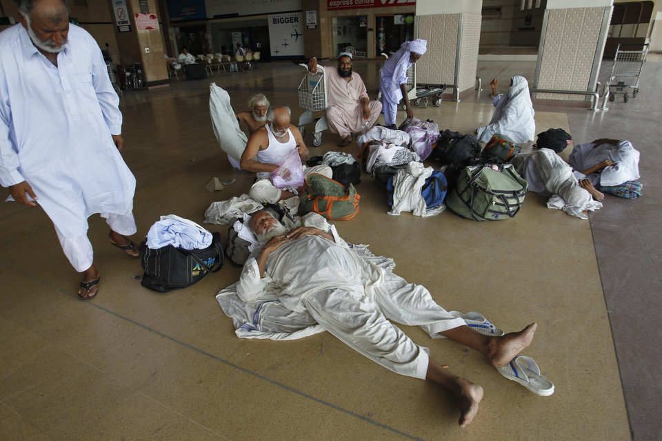Photo - Passengers stranded at the Jinnah International Airport rest in Karachi, Pakistan, Monday, June 9, 2014. The Pakistani Taliban on Monday claimed responsibility for a brazen five-hour assault on the country's busiest airport that saw gunmen disguised as police guards storm the international terminal in Karachi, set off explosions and killing over a dozen of people. (AP Photo/Fareed Khan)