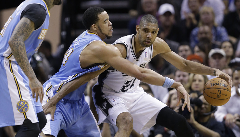 San Antonio Spurs' Tim Duncan (21) is pressured by Denver Nuggets' JaVale McGee, center, during the second half of an NBA basketball game, Wednesday, March 27, 2013, in San Antonio. San Antonio won 100-99. (AP Photo/Eric Gay)