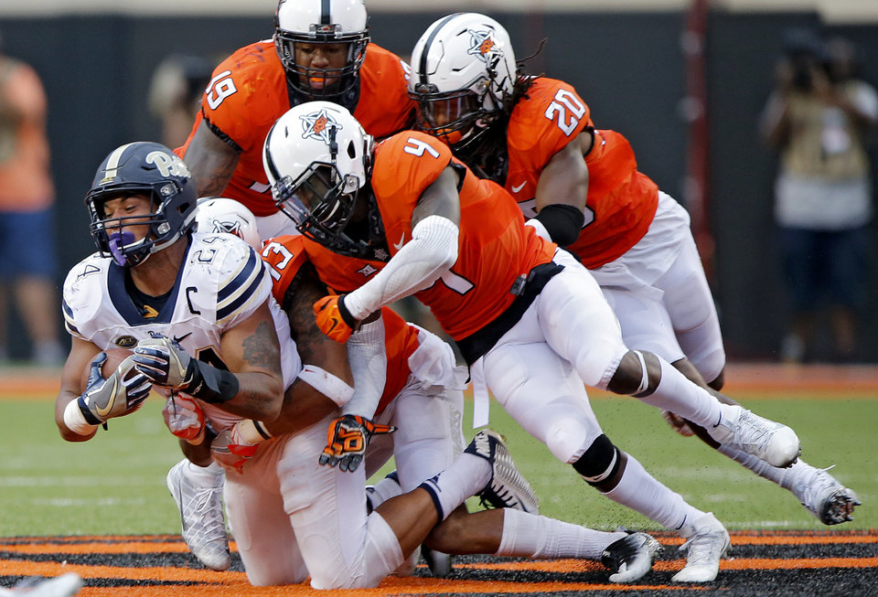 Photo - The Oklahoma State defense brings down Pittsburgh's James Conner (24) during a college football game between the Oklahoma State Cowboys (OSU) and the Pitt Panthers at Boone Pickens Stadium in Stillwater, Okla., Saturday, Sept. 17, 2016. Photo by Chris Landsberger, The Oklahoman