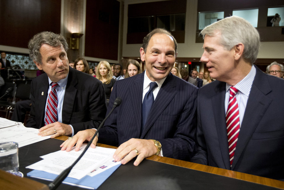 Photo - Veterans Affairs Secretary nominee Robert McDonald of Ohio is flanked by Sens. Sherrod Brown, D-Ohio, left, and Rob Portman, R-Ohio, right, ahead of a Senate Veterans' Affairs Committee hearings to examine his nomination to be Secretary of Veterans Affairs on Capitol Hill in Washington, Tuesday, July 22, 2014.  (AP Photo)