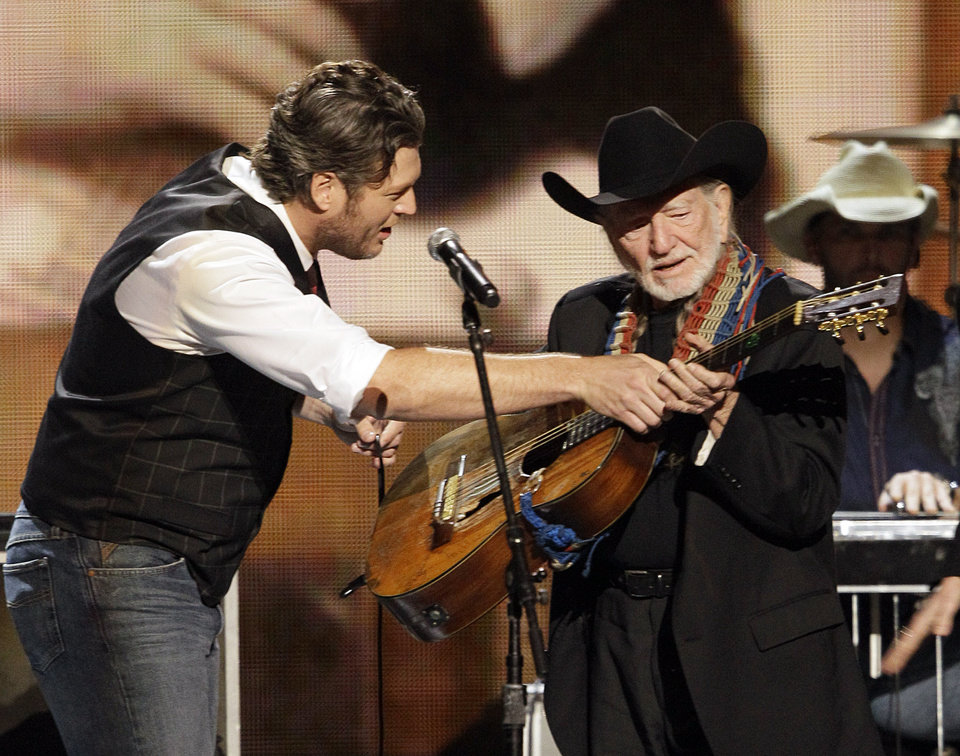 Photo -   Blake Shelton, left, hands a guitar to Lifetime Achievement recipient Willie Nelson at the 46th Annual Country Music Awards at the Bridgestone Arena on Thursday, Nov. 1, 2012, in Nashville, Tenn. (Photo by Wade Payne/Invision/AP)
