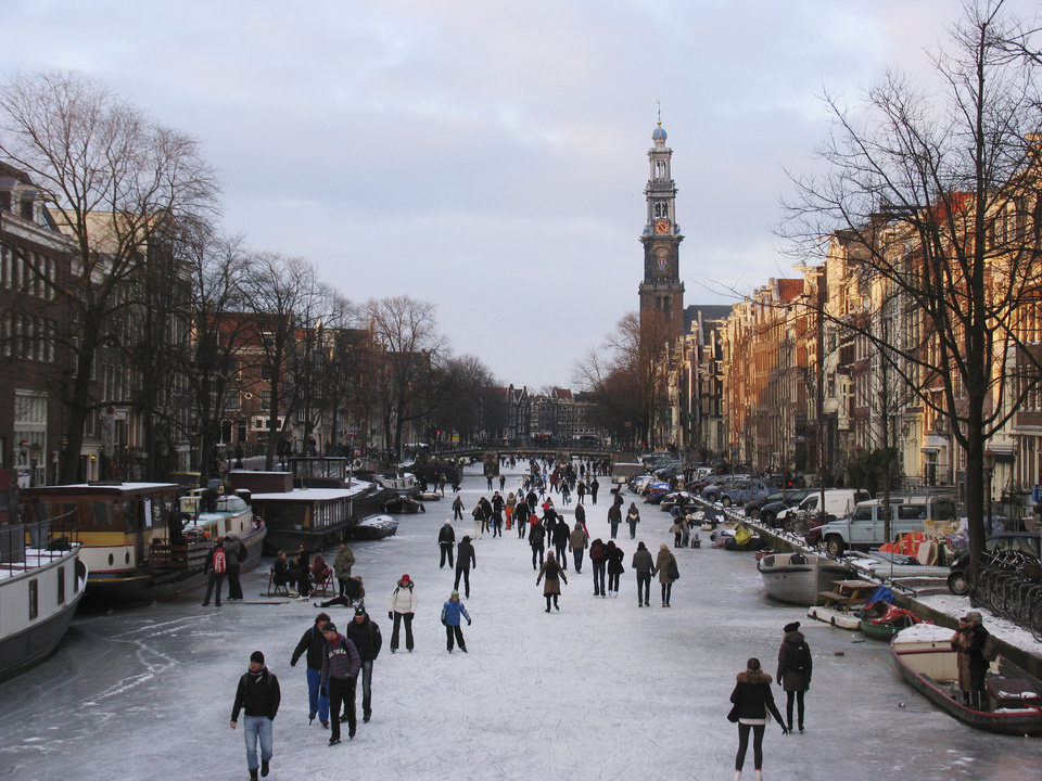 Photo - FILE - In this Feb. 8, 2012, file photo ,people skate on the frozen Prinsengracht canal in Amsterdam. In Amsterdam, when the city's famous canals freeze over, it gives residents a rare opportunity to skate lined by waterfront houses. There is nothing more mythical in Dutch sports than an age-old 11-city race skating across lakes and canals in bone-numbing cold from dawn to dusk. No wonder the Netherlands is the greatest speedskating nation in the world. And with Sven Kramer and Ireen Wust leading the way on big oval in Sochi they are bent on proving it again.  (AP Photo/Margriet Faber, File)