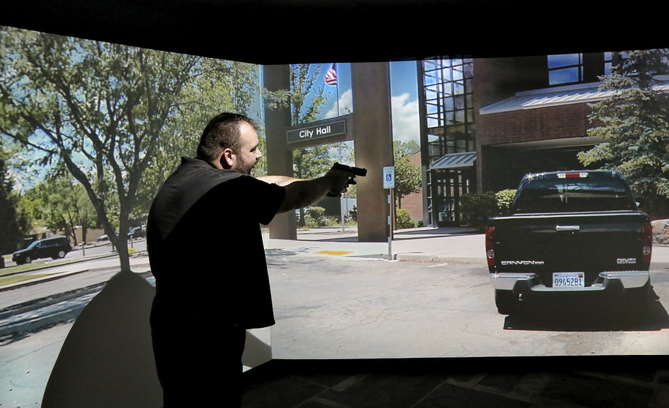 Photo -  Reporter Matt Dinger points his pistol and gives verbal commands to a man inside a vehicle while participating in a training scenario. [Photo by Jim Beckel, The Oklahoman]