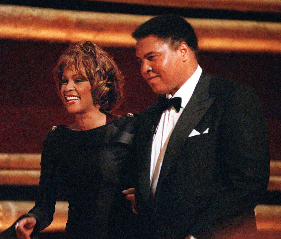 "FILE - In this Oct. 21, 1998 file photo, former World Heavyweight Boxing Champion Muhammad Ali is greeted by singer Whitney Houston as he arrives on stage at New York's Radio City Music Hall to accept a GQ ""Men of the Year"" Award. Whitney Houston, who reigned as pop music's queen until her majestic voice and regal image were ravaged by drug use, has died, Saturday, Feb. 11, 2012. She was 48. (AP Photo/Mitch Jacobson, File) ORG XMIT: NY133"