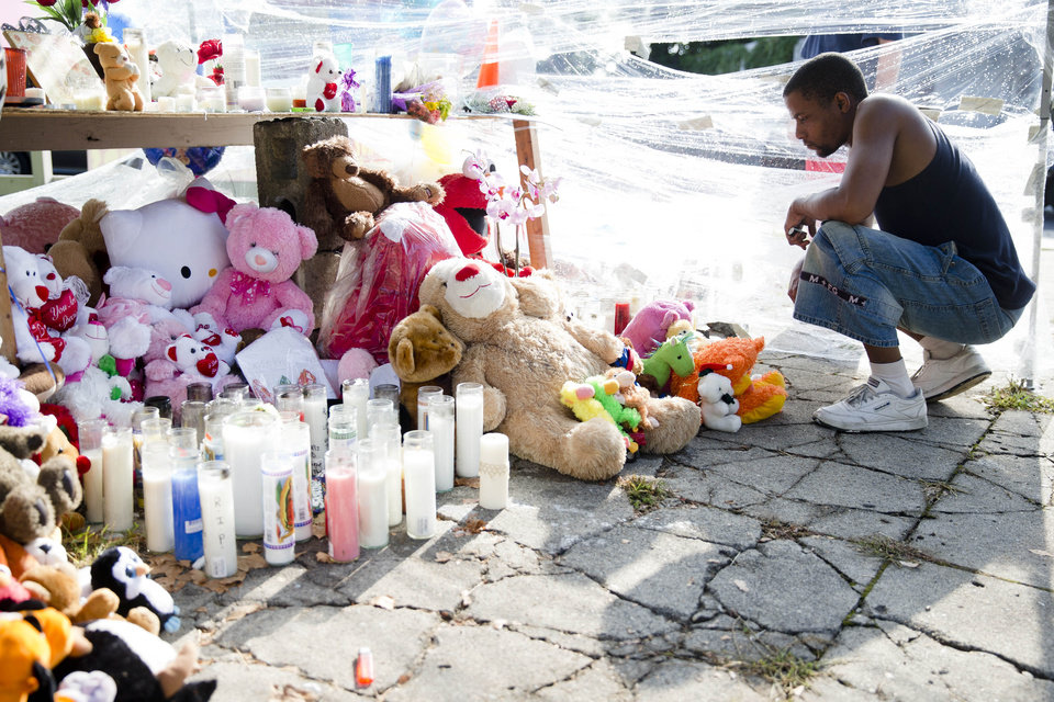Photo - Richard Starchia pays his respects Monday, July 28, 2014, at a makeshift memorial for three children who were killed Friday by a hijacked car that lost control and hit a group of people in Philadelphia. Police investigators are talking to two people in connection with the search for two carjackers who rammed a stolen sport utility vehicle into a family in north Philadelphia, killing three children. (AP Photo/Matt Rourke)