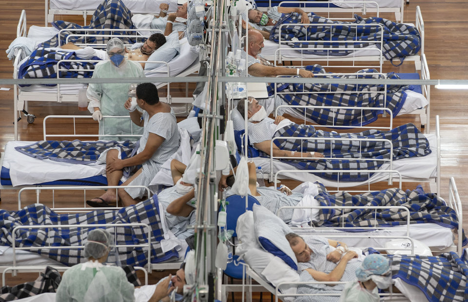 Photo -  FILE - In this Tuesday, June 9, 2020 file photo COVID-19 patients lie on beds in a field hospital built inside a gym in Santo Andre, on the outskirts of Sao Paulo, Brazil. For months, experts have warned of a potential nightmare scenario: After overwhelming health systems in some of the world's wealthiest regions, the coronavirus gains a foothold in poor or war-torn countries ill-equipped to contain it and sweeps through the population. (AP Photo/Andre Penner, File)