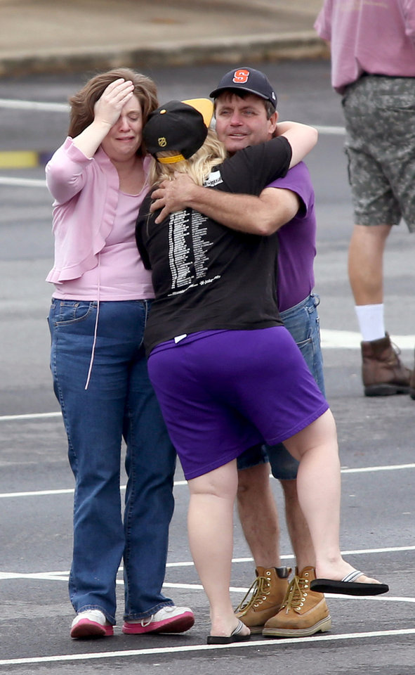 Photo - A FedEx employee, right, is consoled as other FedEx employees wait to meet their family at a nearby business after they were evacuated from the Airport Road FedEx facility after an early morning shooting Tuesday April 29, 2014, in Kennesaw, Ga. At least six people were wounded before police swarmed the facility. The shooter was found dead from an apparent self-inflicted gunshot wound. (AP Photo/Jason Getz)