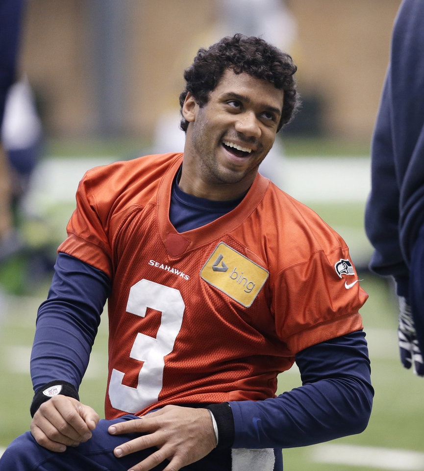 Photo - Seattle Seahawks quarterback Russell Wilson smiles as he stretches for NFL football practice Tuesday, Jan. 7, 2014, in Kirkland, Wash. The Seahawks play the New Orleans Saints Saturday in an NFC divisional playoff game. (AP Photo/Elaine Thompson)