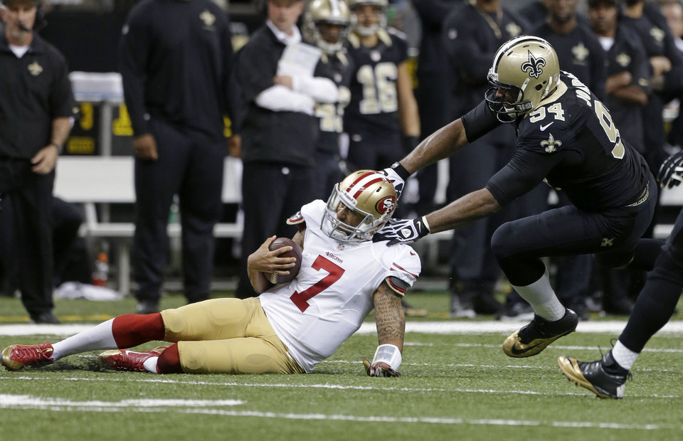 Photo - San Francisco 49ers quarterback Colin Kaepernick (7) slides as he is stopped by New Orleans Saints defensive end Cameron Jordan (94) in the first half of an NFL football game in New Orleans, Sunday, Nov. 17, 2013. (AP Photo/Dave Martin)